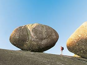 hiking past a boulder