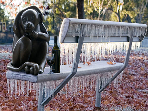 Statue of a brass monkey on frosty chair