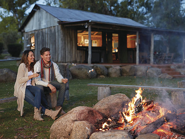 Couple enjoying Granite Belt wine in front of a campfire Diamondvale Cottages in StanthorpeCouple enjoying a campfire Diamondvale Cottages in Stanthorpe