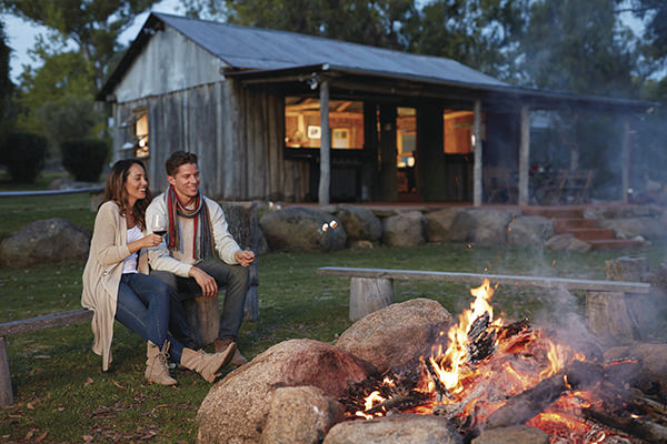 Couple enjoying Granite Belt wine in front of a campfire at Diamondvale Cottages