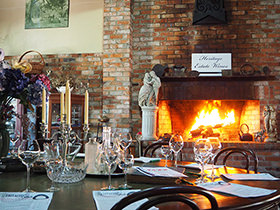 Heritage Estate Wines dining table in front of open fire