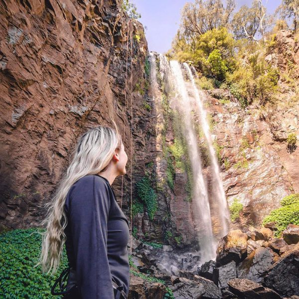 Girl in front of Queen MAry Falls at Killarney